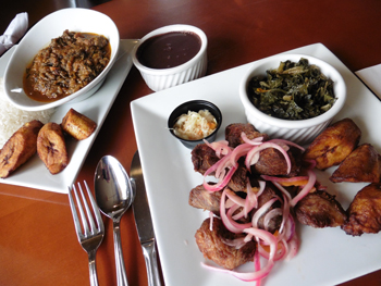 Haiti's distinctive dish called Legume is at left, with fried plantains. At right, Griot with pikliz slaw and collard greens.