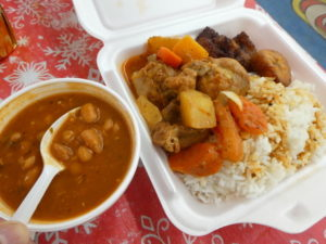 A side of pinto beans with chicken stew and fried plantains.