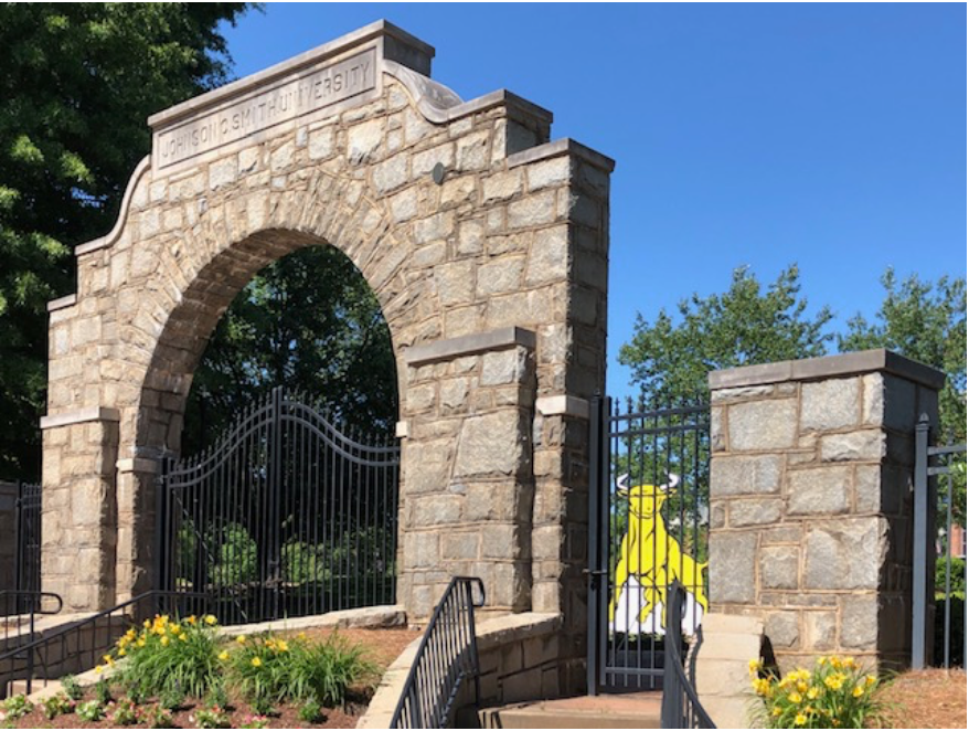 "Biddle Institute started right after the Civil War to train ""teachers and preachers"" – leaders among the newly freed African American population of the South. Its success attracted the Johnson C. Smith family as funders and the college was renamed in their honor in 1923, the year this stone gateway was built.  In the photo, can you glimpse the bright yellow cut-out? It's the Golden Bull, JCSU's mascot, placed as part of the University's 150th birthday celebration in 2017."