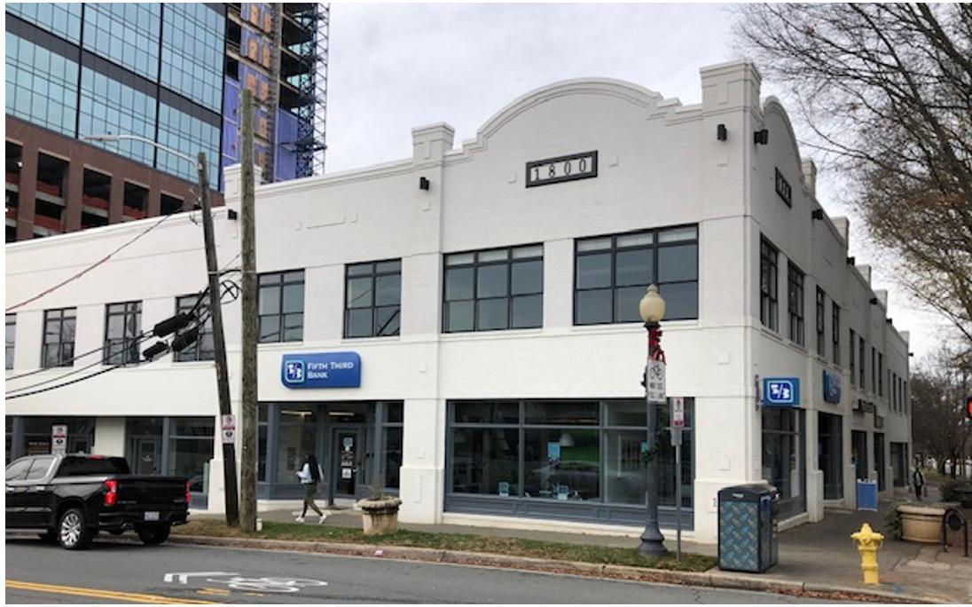 This two-story brick row looks older, but it dates from 1999. After chasing suburban dreams, Americans were beginning to rediscover the joys of urban living. Developer Tony Pressley took a chance on constructing these small retail units with living space upstairs. A success!